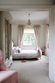 Feminine bedroom in soft shades of pink with old, white wardrobe, double bed with upholstered footer and pretty, gathered pale curtains in background. Elegant country-house ambiance.