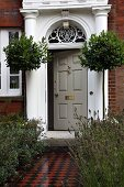 Bay trees flanking stately entrance of English country house with brick facade and mosaic path edged by beds of lavender