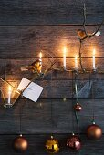 Christmas baubles hanging on wooden wall and lit candles on twigs in candle clips