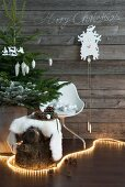 Fairy lights snaking around tree stump with fur blanket and decorated Christmas tree in front of cuckoo clock on vintage wooden wall