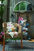 Wicker chair decorated with green beads and floral cushions on patterned rug; colourful postcards and memorabilia on old barn wall