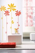 Sunflower wall stickers on partition, white cubic stools and red floor cushion