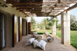 Terrace of Mediterranean house with pergola on concrete pillars with view of garden