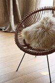 Fur cushion on retro metal chair on wooden floor