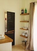 Corner of modern kitchen - fitted fridge-freezer with blackboards on doors next to crockery on shelves