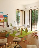 Modern child's bedroom with white shell chairs and table on green rug in front of open terrace door