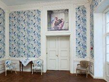 Elegantes Zimmer mit blau-weiss gemusterter Tapete und weisser Holzverkleidung