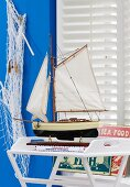 Maritime decor with sailing boat, fisherman's net & metal signs