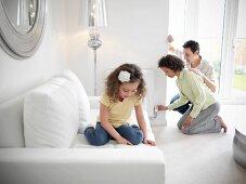 Mädchen liest ein Buch auf dem Sofa, die Eltern stellen im Hintergrund den Heizkörper ein