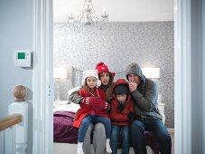 Familie mit Winterjacken und Mützen gekleidet, sitzt frierend im Schlafzimmer