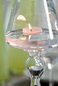 Lit tealight in glass candlestick