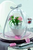 Spring posy in vase on dish under glass cover