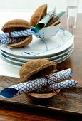Rolled origami paper in decorative nut shells and crockery with white and blue painted detail on table