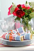 Rolled linen napkins with multicoloured stripes and name tags on stack of plates in front of summer bouquet in vase
