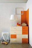 Dark orange accents on white chest of drawers and wall in corner of room