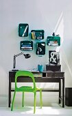 Grass green plastic chair at black wooden bureau and modular, plastic box shelves with rounded corners in emerald green mounted on wall