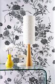 Yellow vase next to table lamp with white lampshade and wooden base on bent glass console table against wall with black and white floral wallpaper