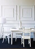 White dining set and white standard lamp against white, coffered, wooden wall combined with black sisal carpet