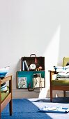 Open suitcases upcycled as shelves mounted on wall between fifties-style upholstered armchairs
