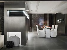 Set table with white upholstered chairs on a gray tile floor in front of a dramatically lit built-in shelf