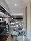 Tea lights in elegant glass candle holders on hammered metal side tables in a modern living room