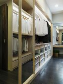 Open cupboard with clothing hung on rods in a dressing room