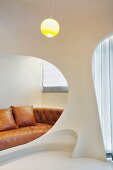 Futuristic room design with openings and view of a light brown leather sofa