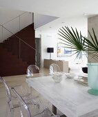 Dining area with plexiglass Ghost chairs at white-stained table; dark, sculptural staircase contrasting with pale, open-plan interior