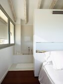 Double bed against wardrobe partition screening ensuite bathroom with white-stained ceiling beams and continuous ribbon window on one side