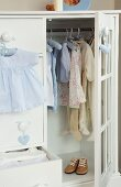White wardrobe with open door showing child's clothes hanging on rail