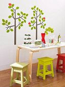 Dining table and colourful stools in front of tree-motif wall stickers