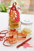 Copper Christmas biscuit cutters in front of glass storage jars of biscuits