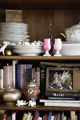 Antique shelf with books, decorative objects and crockery