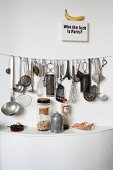 Assorted kitchen utensils on a white wall
