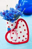 Heart-shaped pot holder in front of fabric-covered beaker of cornflowers