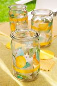 Lit hurricane candles in preserving jars with fruit motifs on pale yellow tablecloth