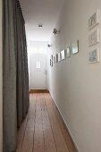 Schmaler Hausflur mit Dielenboden und weisse Eingangstür mit Fenster
