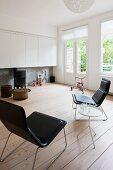 Moderne Sessel mit schwarzem Lederbezug und Beistelltisch auf Dielenboden vor Wand mit Kanonenofen und weissen Hängeschränken