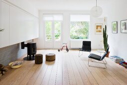 Minimalist living room with black armchairs on wooden floor and pouffes in front of small, round, iron stove in front of terrace doors with view of garden