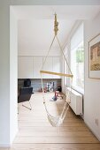 Hammock swing in doorway and view into minimalist living room with black armchair and white wall units