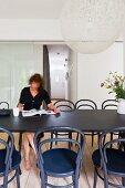 Frau liest am Esstisch - Kugelförmige Designer Hängeleuchte aus weißem Geflecht über Tisch mit schwarzen Thonetstühlen