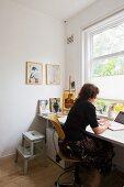 Frau am Arbeitstisch vor Fenster in Zimmerecke