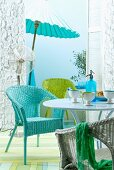 Set of wicker chairs in turquoise, green and white at round table; fan and parasol in front of sky blue wall in background