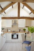 Bright kitchen with white cupboards and dining area below gable beams