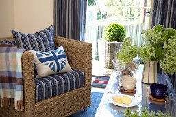 Sea grass armchair with scatter cushions and flowers and cups on coffee table