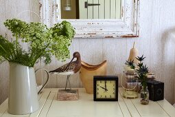 Flowers, alarm clock and ornaments on white table