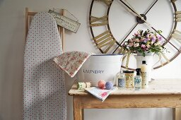 Laundry utensils on rustic wooden table below vintage wall clock