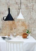 White and black funnels upcycled as original lampshades above stack of toast on kitchen table