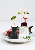 Party skewers stuck in lids of salt cellars and wooden fish on plate