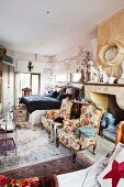 Two Rococo armchairs in front of disused fireplace niche in bedroom crammed with furniture